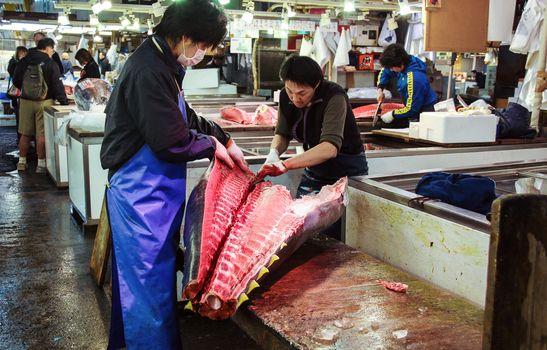 TOKYO, JAPAN - APRIL 05, 2012: Workers cut big tuna at famous Tsukiji fish market in Tokyo, Japan