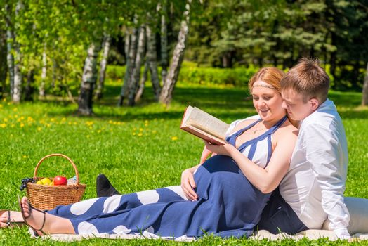 young pregnant couple in a park reading a book about pregnancy a