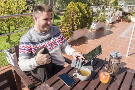 Happy man having breakfast with technology in the garden