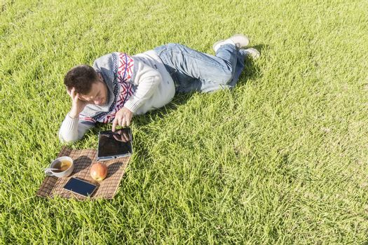 Man having breakfast lying on the grass in the garden with technology