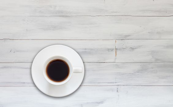 Top view of cup of fresh espresso on white wooden background