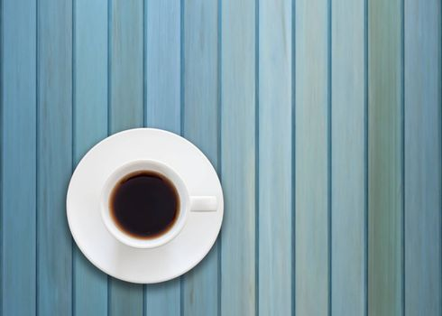 Top view of cup of fresh espresso on blue wooden background