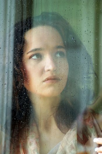 Woman with sad smile behind a wet window
