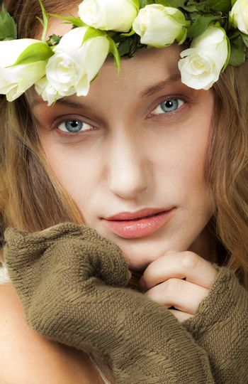 A portrait of beautiful young woman with colorful eyes and white roses wreath.