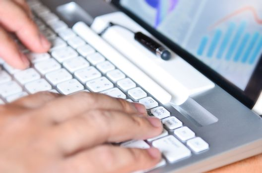 Businessman hands busy using laptop at office desk