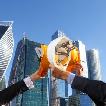 Group of business people clinking their helmets as a success on skyscrapers background, construction finished concept