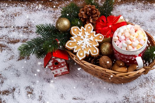 hot chocolate with melted marshmallows,ginger bread cookies,nuts in wicker basket on snow. copy space