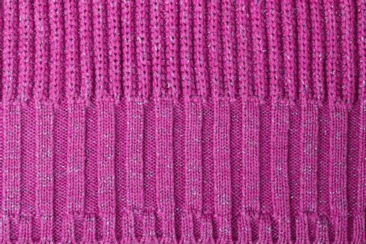 Texture of pink knitted woolen fabric for wallpaper and an abstract background