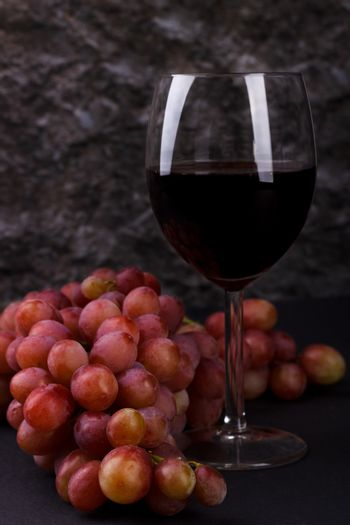 Red glass of wine and grapes
