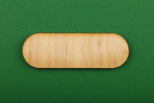 Figured shaped wooden sign on green background