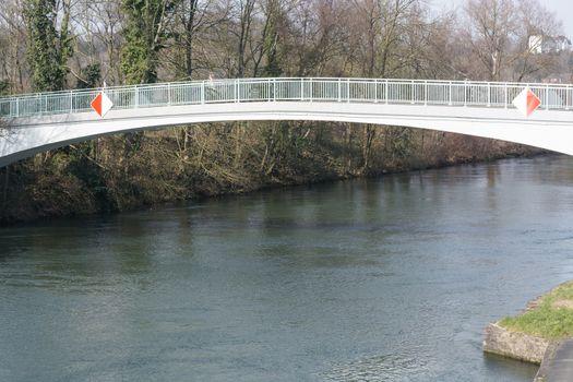 Fußgänger Brücke aus Stahl in Bogenkunstruktion über den Flu