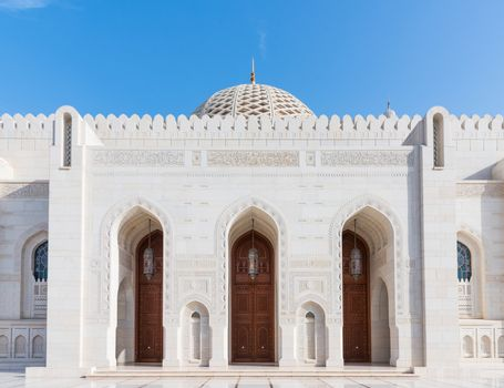 Exterior detail with entrance doors and the dome in the background of the Sultan Qaboos Grand Mosque in Muscat, the main mosque of The Sultanate of Oman.