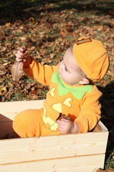 Brunette baby girl wearing an orange halloween pumpkin outfit