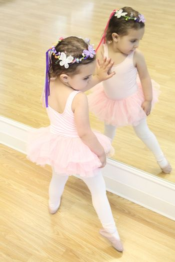 Little ballet girl standing in front of a mirror