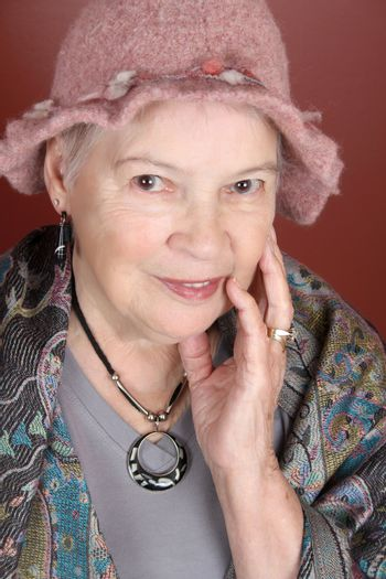 Senior lady wearing a pink hat in studio setting