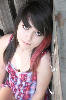 Beautiful brunette girl sitting amongst rustic objects