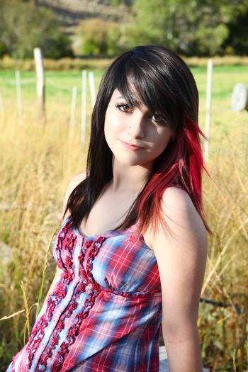 Beautiful brunette girl sitting outside with farmland in background