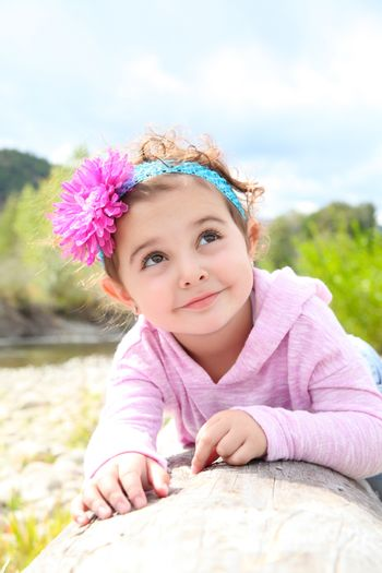 Beautiful brunette toddler playing outside by the river