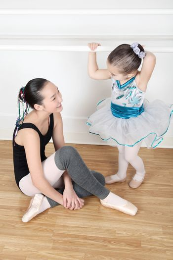Teen dancer and toddler in costume at dance studio