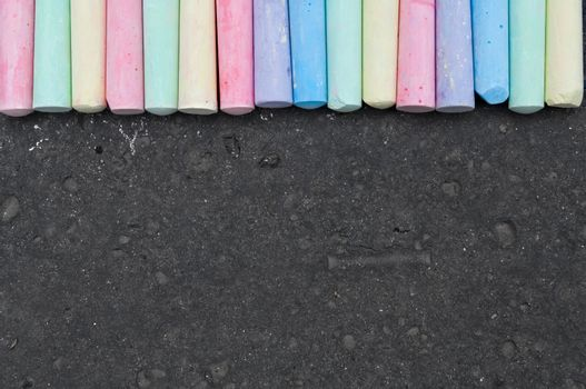 Colorful pastel sidewalk chalk on dark asphalt background. Top view
