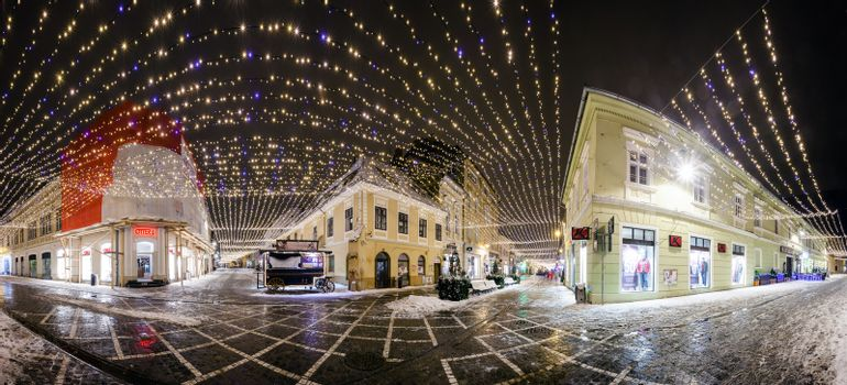 BRASOV, ROMANIA - 15 DECEMBER 2016: Panoramic night view of Republic Street decorated for winter hollidays with  Christmas lights in Brasov old city center, Romania