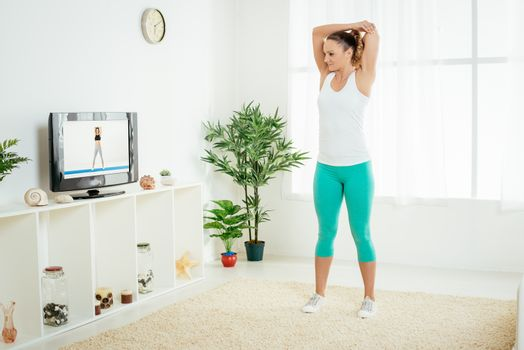 Beautiful young woman stretching out her hands at home in front of the tv.