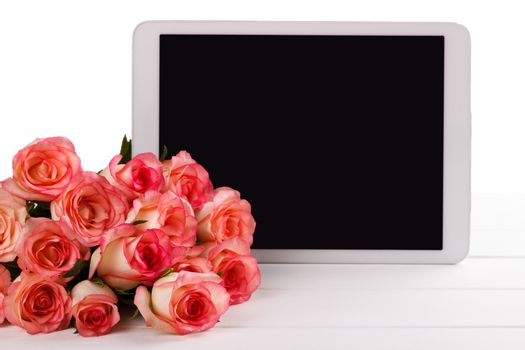 Tablet and pink roses