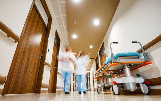 Blurred image of staff member in medical uniformn fixing hospital bed