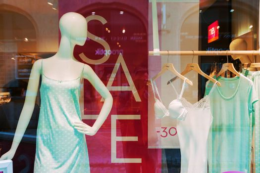 REGENSBURG, GERMANY - JULY 14, 2016: Shop sale window display with mannequin and hanging clothes in Regensburg, Germany