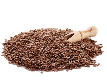 Flax seeds and shovel spice on a white background