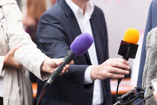 Journalists holding microphones, conducting press interview