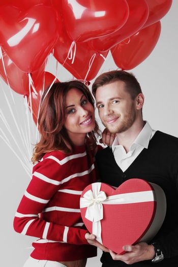 Happy embracing couple in love holding Valentines day gifts and bunch of heart shaped balloons
