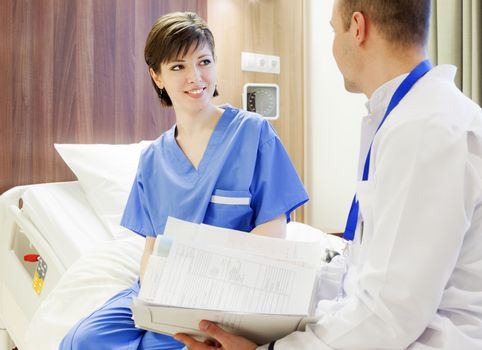 A happy young female patient sitting on a modern electrical hospital bed, smiling at a doctor with files in hands.