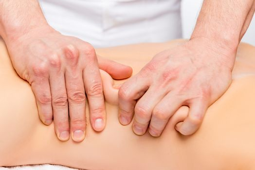 strong male masseur's hands knead the skin and muscles of the ba