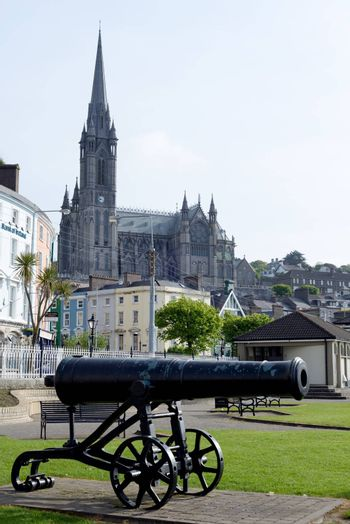 St Colman's Cathedral above cobh town and bay in county cork ireland with canon in foreground