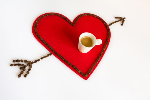Cup of coffee on a red felt heart and arrow in diagonal