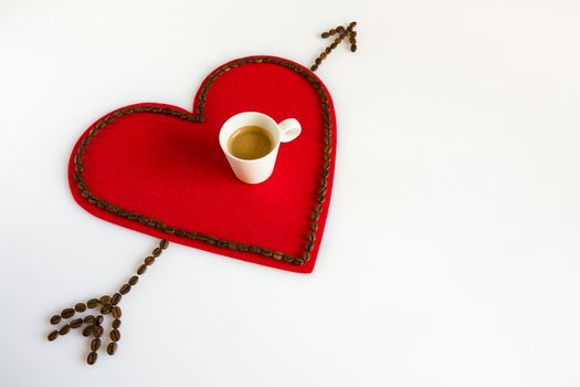 Cup of coffee on a red felt heart and arrow