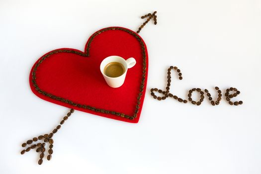 Cup of coffee on a red felt heart with arrow and love