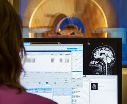 An operator is looking at images of scanned on MRI human brain in modern hospital.