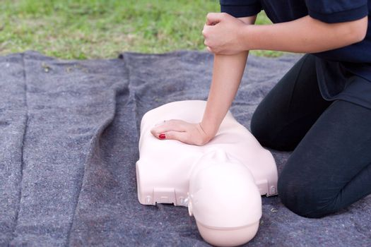 Paramedic demonstrate Cardiopulmonary resuscitation (CPR) on training doll. Heart massage.