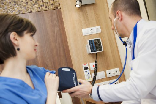 A doctor is measuring the blood pressure of a young female patient in modern hospital.