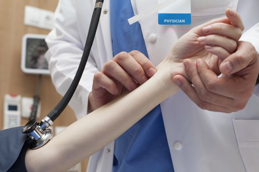 Close-up of a doctor hands measuring the pulse of a patient in hospital.