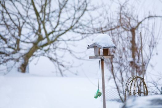 simple homemade wooden birdhouse installed on winter garden in snowy day