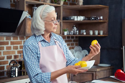 Senior woman in eyeglasses and apron looking at lemons in kitchen