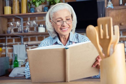 Smiling senior woman in eyeglasses reading cookbook in kitchen