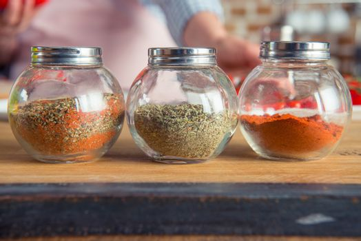 Close-up view of three glass jars with spices