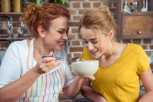Smiling mother and daughter looking in bowl while cooking together in kitchen