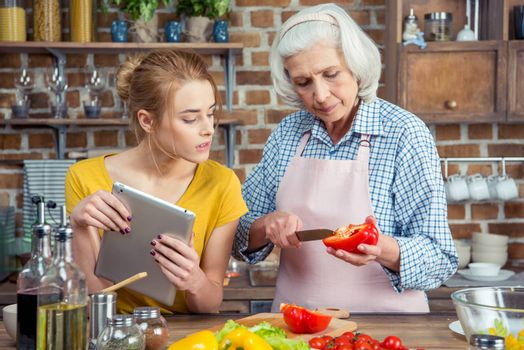 Granddaughter and grandmother using digital tablet while cooking vegetable salad together