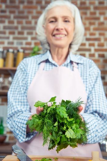 Smiling senior woman holding green herbs in kitchen