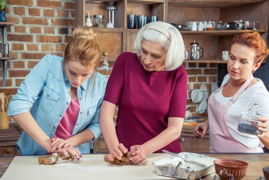 Family of three generations preparing gingerbread cookies kneading dough